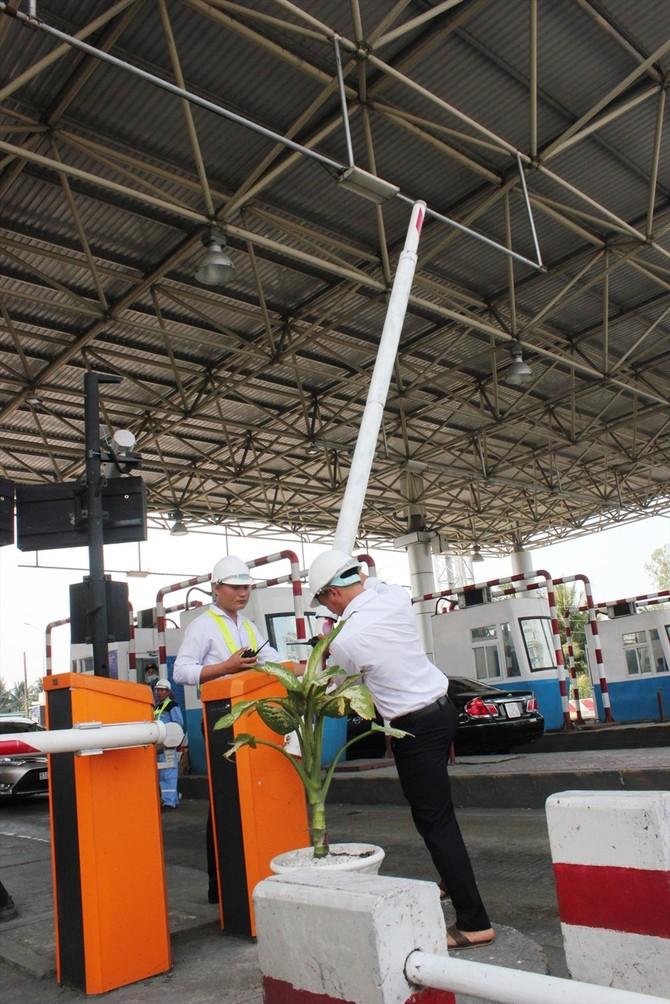 Nhân viên trạm BOT Cai Lậy sửa lại thanh chắn bị tài xế tông (ảnh: Tr.L)